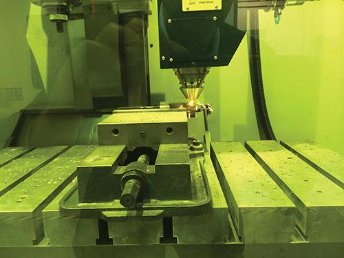 Optomec and MachMotion together developed a retrofit additive manufacturing system for machining centers that is now being used and evaluated at TechSolve. In this photo, the machine is being used to additively grow a feature onto a shaft.